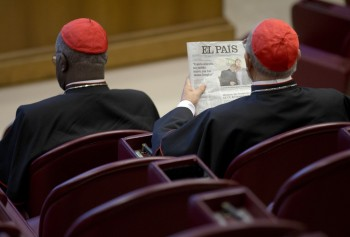 Spanish Cardinal Ricardo Blazquez Perez, right, reads a newspaper showing a picture of gay bishop Krzysztof Charamsa and his partner Eduard before the start of the morning session of the Synod of bishops on family issues, at the Vatican, Friday, Oct. 9, 2015. Last week the Vatican fired Charamsa who came out as gay on the eve of the meeting of the world's bishops. (AP Photo/Alessandra Tarantino)